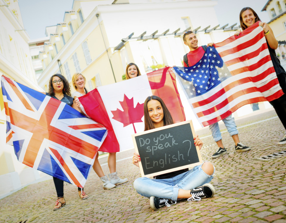 College students learning English with flags and blackboard, outdoors.